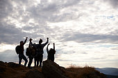 Silhouettes of five young adult friends celebrating at the summit after a mountain hike, back view