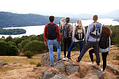 A group of five mixed race young adult friends admire the view after arriving at summit after a mountain hike, back view, close up