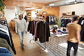 People walking through a busy clothes shop, motion blur