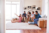 Group Of Friends Relaxing At Home Watching TV Together