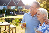 Senior Couple Enjoying Outdoor Summer Drink At Pub