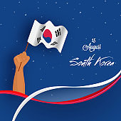 Human hand holding national flag of South Korea on shiny blue background for Korean independence day celebration.