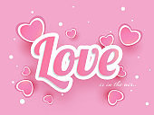 Sticker style text Love decorated with hearts on pink background.