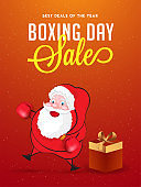 Boxing Day sale banner or poster design, illustration of fighter santa claus with gift box on shiny orange background.