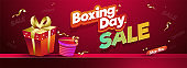 Sale header or poster design, sticker style text Boxing Day with gift boxes on shiny brown background.