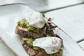 Avocado with poached eggs on toast in trendy hipster restaurant high end