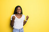 I won. Winning success happy african woman celebrating being a winner on yellow studio background. Victory, delight concept. Human facial emotions concept. Trendy