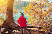 A single man sitting on the river bank on the tree in autumn and looking at the water