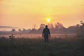 A man stands in the lake shore early in the morning and looks at the sunrise