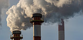 Smoking chimneys of a chemical plant emitting huge amounts of greenhouse gases.Air environment pollution concept.