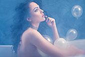 Beautiful woman relaxing in bathtub with balloons. Woman taking a bath in steamy bathroom.