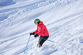 Skiing  Off piste Amateur Winter Sports woman skier skiing in powder snow.   Back country skiing,  at sunny ski resort Dolomites in Italy.