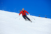 Amateur Winter Sports  alpine skiing. Man snow skier skiing at sunny ski resort. High mountain snowy landscape.  Kronplatz, mountain of the Dolomites in South Tyrol, Italy.