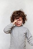 Crying child rubbing eye