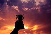 Hand holding winner trophy