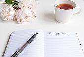 Gratitude journal with pen peonies and tea