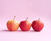 Three red gala apples on pink background