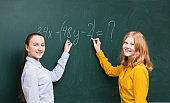 Two girls at the blackboard in a mathematics class