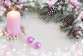 burning candle and Christmas decorations on white wooden background