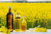 rapeseed oil in field on white wooden table