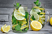 Lemon and herb detox water in a jars on table