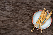 Dry Ginseng Roots on wood background ,Top view with copy space