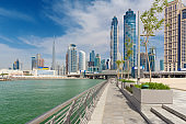Dubai - The skyscrapers over and the promenade of new Canal and Burj Khalifa in the background.