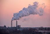 Chimney smoking stack at sunset.