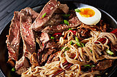 black bowl of Soba with beef and veggies