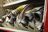 Compartment of rolled up fire hoses on a fireengine. Emergency safety. Protection, rescue from danger.