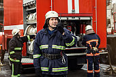 Fireman (firefighters) in action standing  near a firetruck. Emergency safety. Protection, rescue from danger.