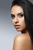 Beautiful model girl with smooth dark hair. Great hair. Black dress. Woman looking away