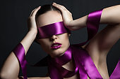 portrait of a girl with a purple ribbon in her eyes. The girl touches her face with her hands.Gray background.