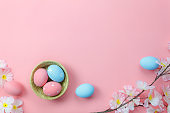 Top view shot of arrangement decoration Happy Easter holiday background concept.Flat lay colorful bunny eggs with accessory ornament floral on modern beautiful pink paper at office desk.pastel tone.