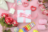 Table top view aerial image of mothers day background concept.Flat lay object essential mom season the white gift box and items on modern pink paper at home office desk.Decoration for development.