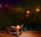 Traditional female carnival venetian mask  on table .Masquerade  mask on  glitter background.Mardi Gras.