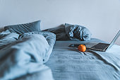 empty messy grey bed with laptop. lifestyle rest in bed concept