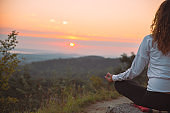 woman do yoga exercises at top of the hill on sunrise
