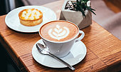 Cup of coffee and cake on a wooden table in a cafe