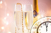 New Year champagne glasses with fireworks and clock