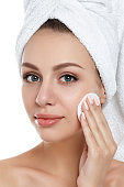 Young woman with towel on her hair cleaning makeup
