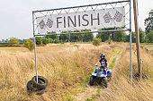 Young dutch man driving quad towards finish