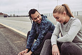 Smiling young couple sitting on a curb after jogging together