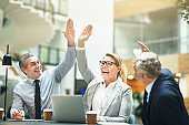 Mature businesspeople cheering and high fiving together in an office