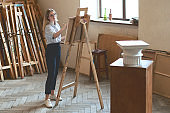 Young beautiful girl student is drawing a Doric capital with a pencil on a wooden easel as her university assignment
