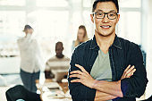 Young Asian businessman smiling with colleagues working in the background
