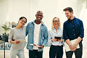 Diverse young businesspeople laughing together in a bright modern office