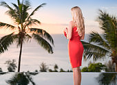 Woman in a Red Dress at a tropical Cocktail Party watching the Sunset, Palm Tree Background