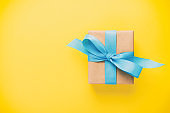 gift wrapped and decorated with blue bow on yellow background with copy space vintage, toned. Flat lay, top view