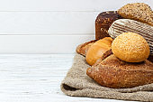 Plenty bread background. Bakery and grocery concept. Fresh, healthy rye and white loaves, sprinkled flour on sackcloth and rustic wood table, food closeup